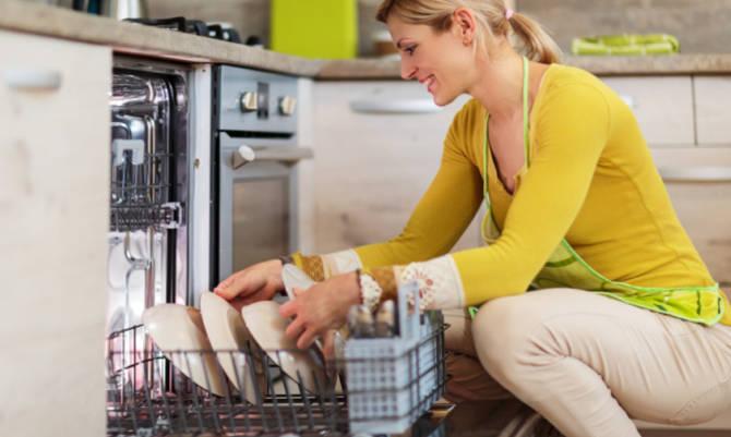 donna sorridente utilizza lavastoviglie in cucina