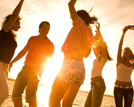 Giovani danzano sulla spiaggia