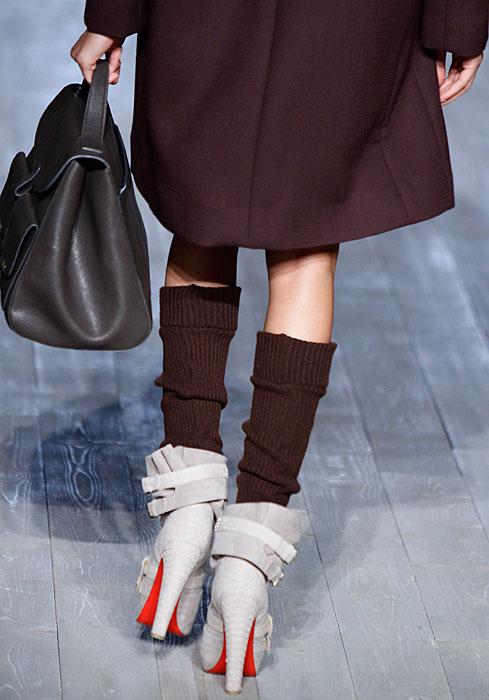 Victoria Beckham - dettaglio scarpe alte con borsa a mano