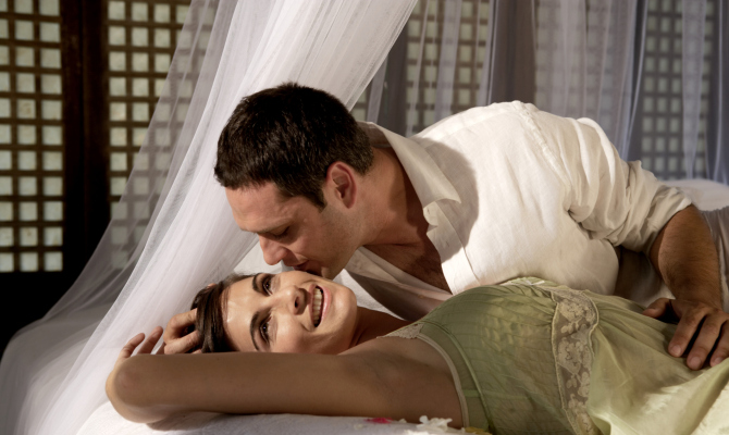 coppia sdraiata a letto con zanzariera a baldacchino