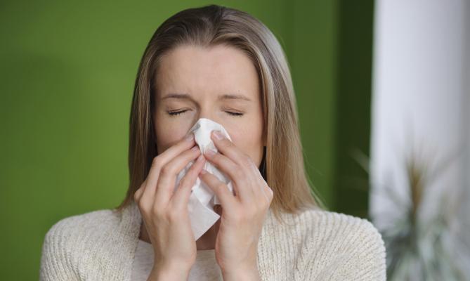 ragazza raffreddata si soffia il naso