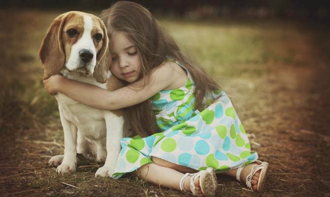 una bambina abbraccia un cane