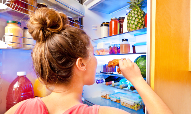ragazza estrae alimento dal frigorifeto