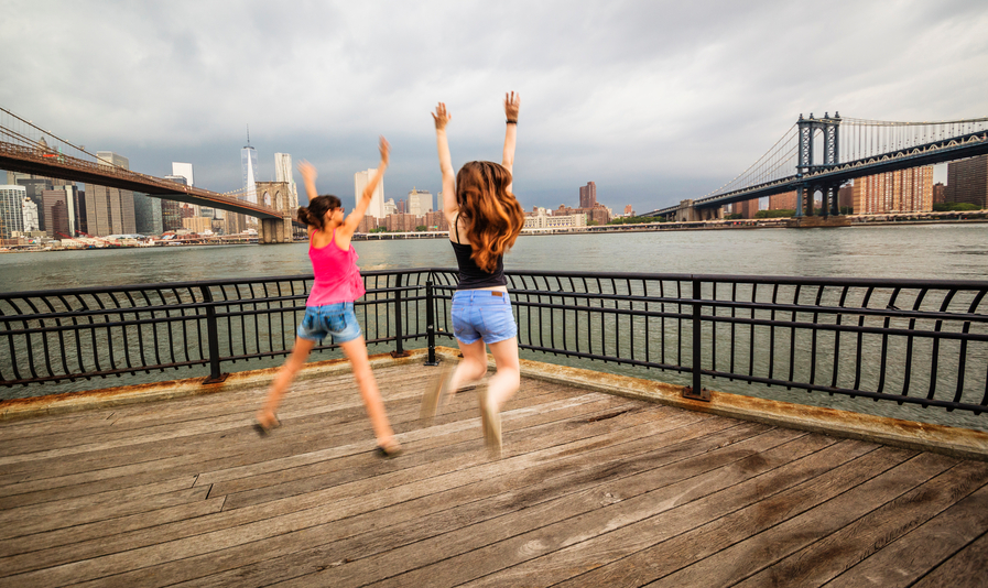 New York, bambine che saltano con panorama su Manhattan