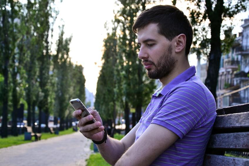 Ragazzo seduto su panchina con smartphone