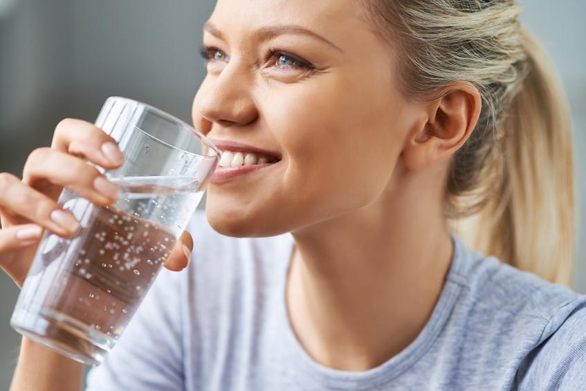 Donna che beve un bicchiere d'acqua