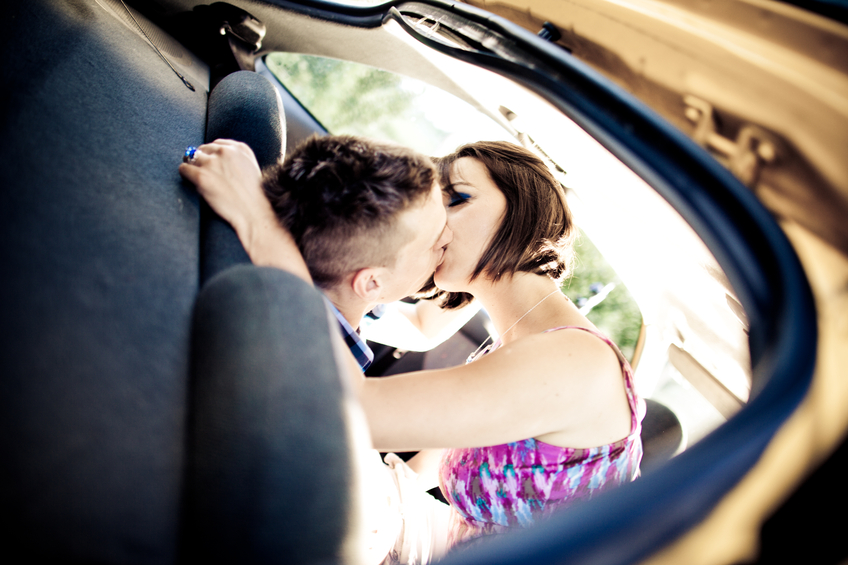 Young couple making out on a back seat in the car.