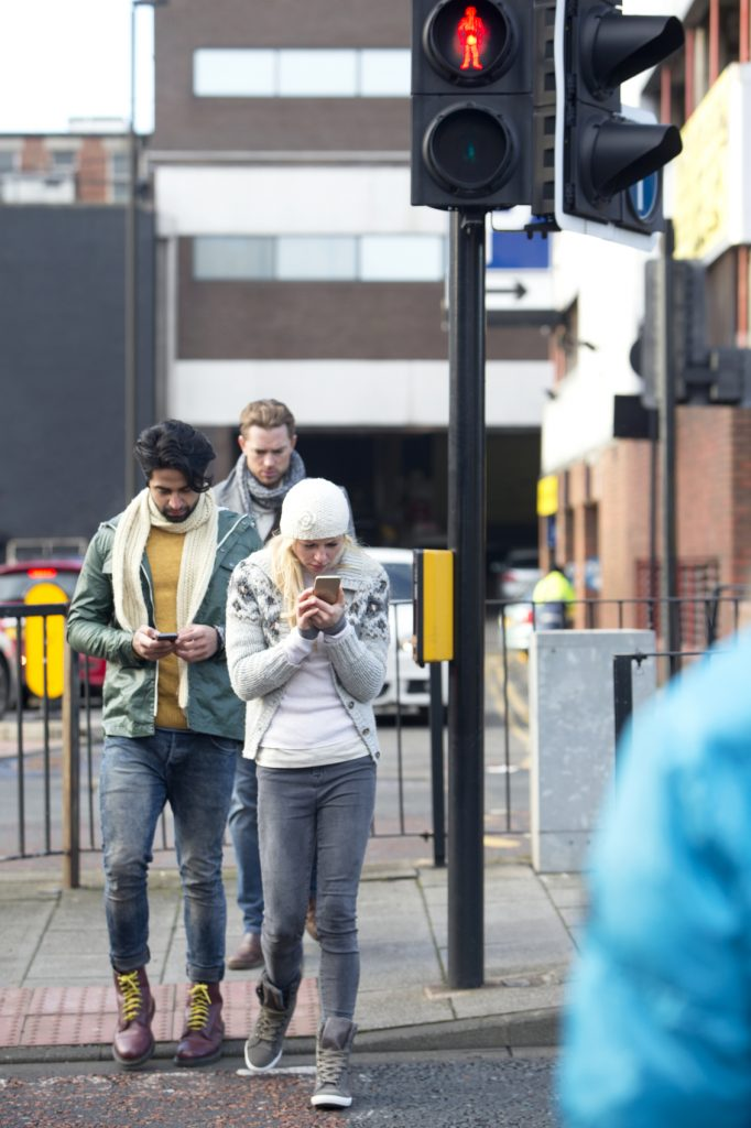 Young people looking at his mobile telephone while crossing a road.