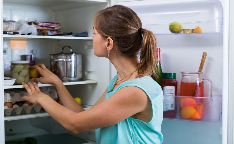donna che sistema gli alimenti sui ripiani del frigo