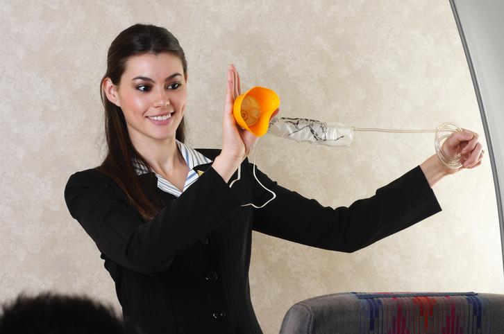 Hostess in aereo con la maschera d'ossigeno