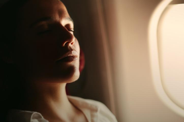 Donna che si rilassa in aereo con esercizi di yoga