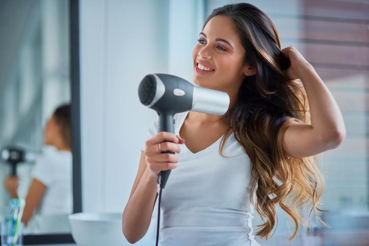 donna asciuga capelli con il phon