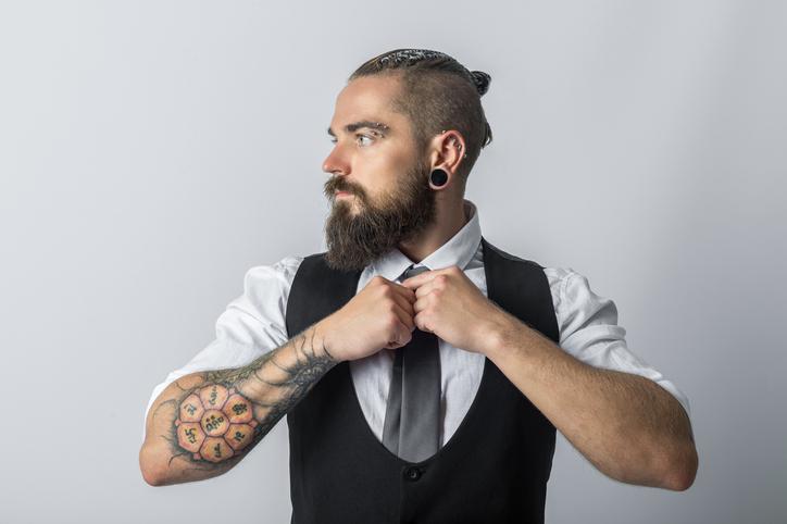 uomo con barba, baffo, piercing e tatuaggi