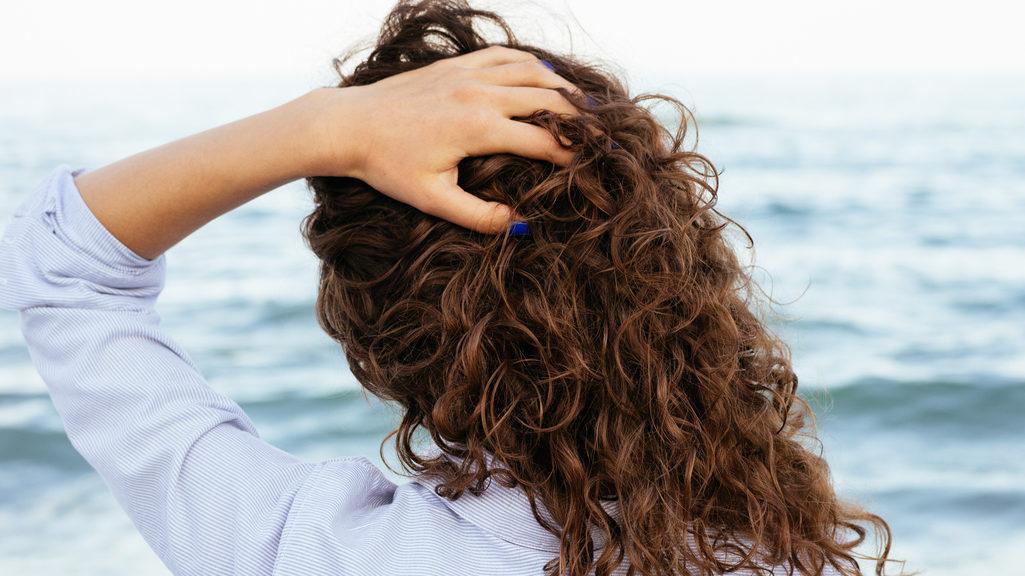 donna con capelli ricci al vento