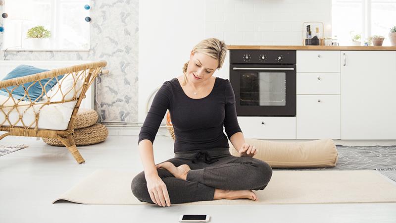 donna che fa meditazione seguendo un corso online