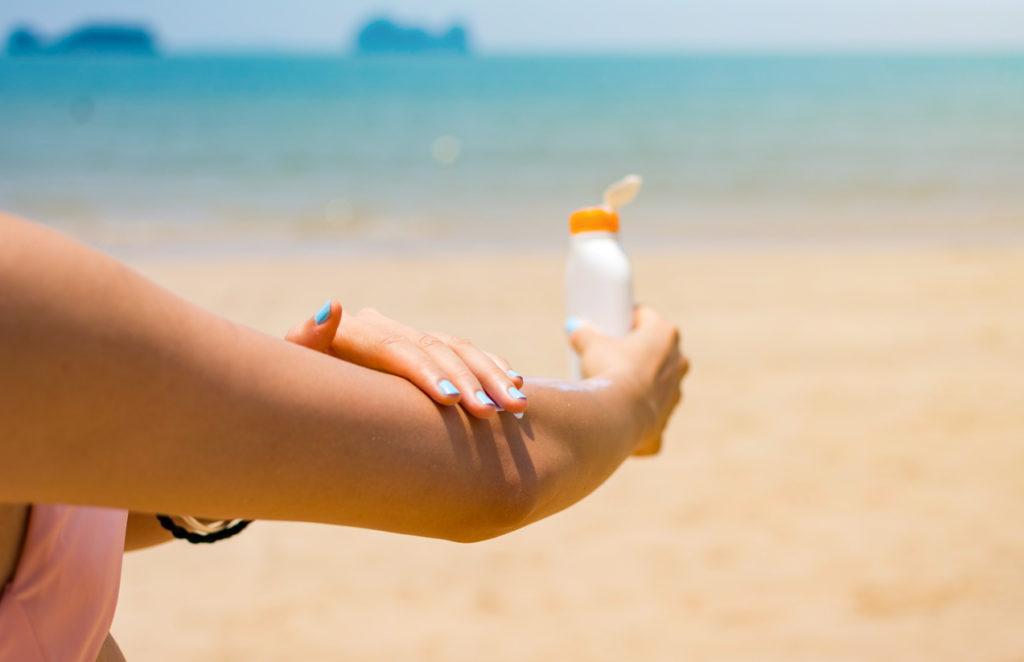 donna che applica crema solare sul braccio
