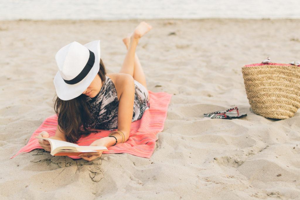 ragazza sulla spiaggia che legge un libro
