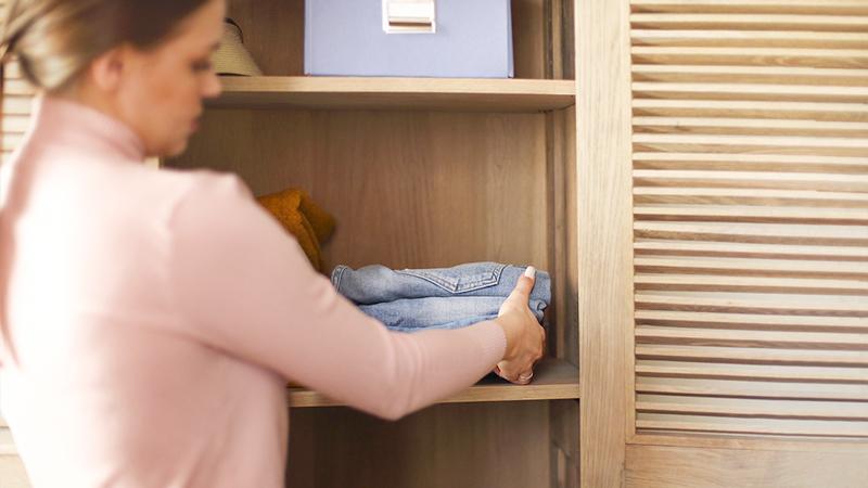 donna che ordina l'armadio
