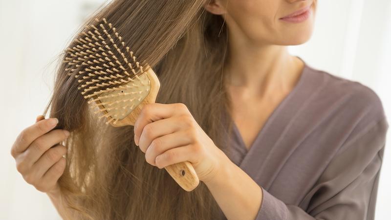 donna che si spazzola i capelli lunghi